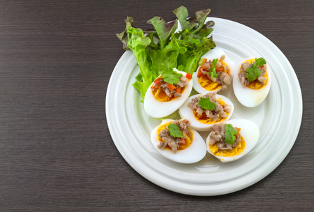 Close up salted egg salad , mix many vegetable ,Mix boiled egg ,Thai food in white dish on black wooden background.