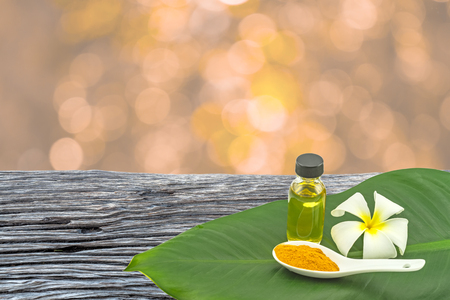 White frangipani flower(Plumeria spp.,Apocynaceae,Pagoda tree, Temple tree),turmeric powder in white spoon and massage oil in green leaf on wooden and orange bokeh background. Stock Photo