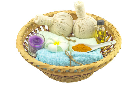 spp: Spa herbal compressing ball , white frangipani flowers (Plumeria spp flower , Apocynaceae flower, Pagoda tree flower, Temple tree flower) , turmeric powder in white spoon massage oil and blue faric  on bamboo basket isolate on white background.