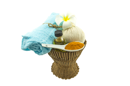 spp: Spa herbal compressing ball , white frangipani flowers (Plumeria spp flower , Apocynaceae flower, Pagoda tree flower, Temple tree flower) , turmeric powder in white spoon massage oil and blue faric  on bamboo basket isolate on white background.Saved with  Stock Photo