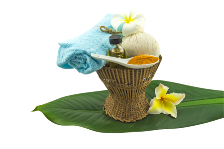 Spa herbal compressing ball , white frangipani flower (Plumeria spp, Apocynaceae flower, Pagoda tree,Temple tree),turmeric powder in white spoon massage oil and blue faric in bamboo basket and green leaf tree  isolate on white background.Saved with clippi