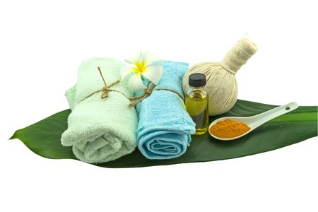 Spa herbal compressing ball , white frangipani flowers (Plumeria spp flower , Apocynaceae flower, Pagoda tree flower, Temple tree flower) , turmeric powder in white spoon massage oil and blue faric in green leaf isolate on white background.