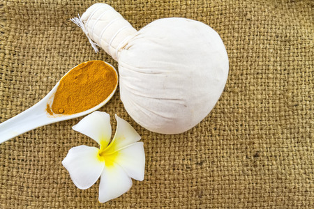 Spa herbal compressing ball , white frangipani flowers (Plumeria spp , Apocynaceae, Pagoda tree, Temple tree) and turmeric powder in wooden spoon on brown sack fabric background Stock Photo