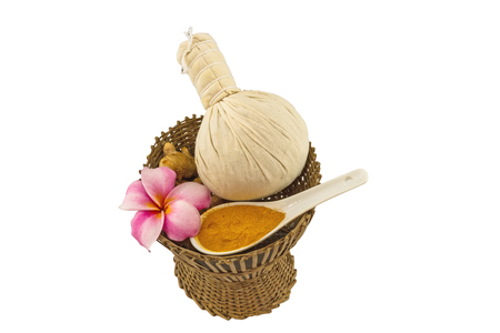 spp: Spa herbal compressing ball , white frangipani flowers (Plumeria spp , Apocynaceae, Pagoda tree, Temple tree) , turmeric powder in white  spoon and candle on bamboo basket isolate on white  background.Saved with clipping path.
