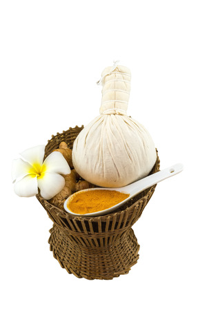 spp: Spa herbal compressing ball , white frangipani flowers (Plumeria spp , Apocynaceae, Pagoda tree, Temple tree) , turmeric powder in white  spoon and candle in bamboo basket  on white background.Saved with clipping path.