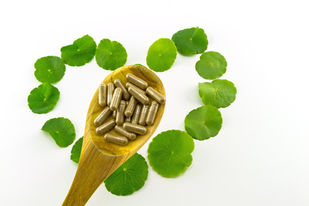 holistic view: Heart shape of green Asiatic Pennywort (Centella asiatica , Hydrocotyle umbellata L or Water pennywort ) and colorful pill in wooden spoon on white background