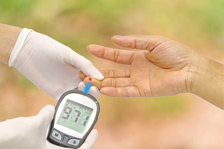Hand of doctor checking for blood glucose meter, the blood sugar value is measured on a finger and pink bokeh background. Stock Photo