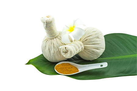 Spa herbal compressing ball , white frangipani flowers (Plumeria spp flower , Apocynaceae flower, Pagoda tree flower, Temple tree flower) , turmeric powder in white spoon in green leaf isolate on white background.Saved with clipping path