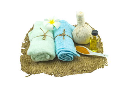 Spa herbal compressing ball , white frangipani flowers (Plumeria spp flower , Apocynaceae flower, Pagoda tree flower, Temple tree flower) , turmeric powder in white spoon massage oil and blue faric in sisal isolate on white background. Stock Photo