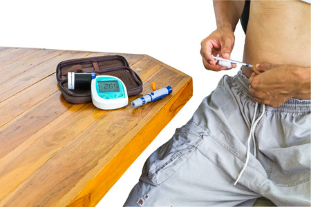 diabetes meter kit: Diabetes patient gets an insulin injection in abdomen area and equipment of  blood glucose meter test kit on table over white background.