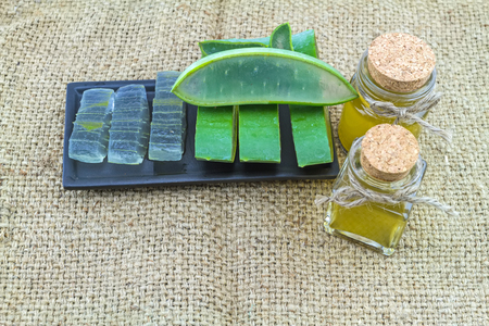 Fresh aloe vera gel on black ceramic dish with aloe  vera essential oil and  color pill on  fabric sack Stock Photo