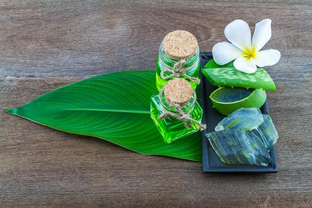 aloe barbadensis: Slice Aloe Vera (Aloe barbadensis Mill.,Star cactus,  Aloin, Jafferabad or Barbados)  Spa compressing ball and Aloe vera essential oil in green leaf on wooden Stock Photo