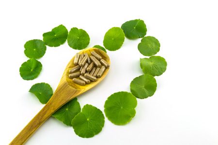 Heart shape of green Asiatic Pennywort (Centella asiatica , Hydrocotyle umbellata L or Water pennywort ) and colorful pill in wooden spoon on white background
