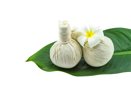 Spa herbal compressing ball and white frangipani flowers (Plumeria spp flower , Apocynaceae flower, Pagoda tree flower, Temple tree flower)  in green leaf isolate on white background.Saved with clipping path