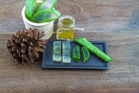 Fresh aloe vera gel on black ceramic dish with aloe  vera essential oil and pine  on wooden table