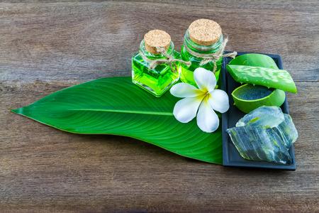 Slice Aloe Vera (Aloe barbadensis Mill.,Star cactus,  Aloin, Jafferabad or Barbados)  white frangipani flowers  and Aloe vera essential oil in green leaf on wooden Stock Photo