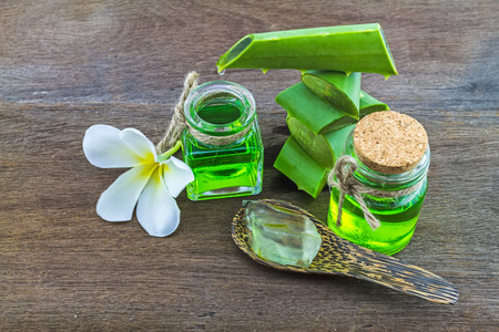 Slice Aloe Vera (Aloe barbadensis Mill.,Star cactus,  Aloin, Jafferabad or Barbados)  white frangipani flowers  and Aloe vera essential oil  on wooden