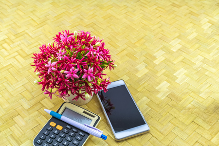 Colorful flower Drunen sailor in vase and calculator,mobile phone,pen  on bamboo weave background Stock Photo