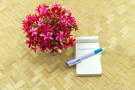 Colorful flower Drunen sailor in vase and paper note with word INSPIRATION on bamboo weave background