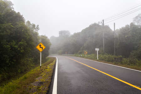 Windy forest road with a curve sign on a foggy day  at Doi Inthanon national park, Thailand