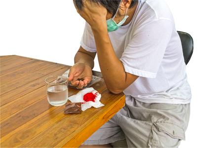 Patiënt man van tuberculose met anti-tuberculose medicijnen bij de hand en bloedspuwing op witte achtergrond. Opgeslagen met uitknippad.