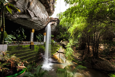 Motion blurred water and children play in  the temple under waterfall Wat Tham Heo Sin Chai waterfall. Kaeng Tana National Park, Ubonratchathani, Thailand