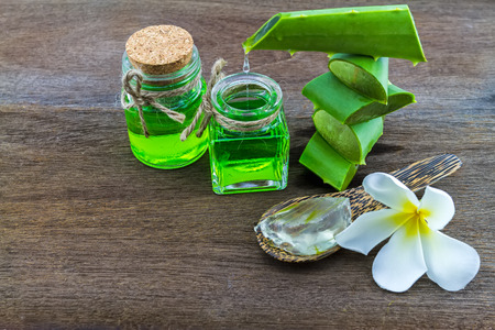 Slice Aloe Vera (Aloe barbadensis Mill, Star cactus,  Aloin, Jafferabad or Barbados)  white frangipani flowers  and Aloe vera essential oil  on wooden