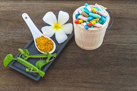 Spa herbal (white frangipani flowers, turmeric powder in white spoon, pill, Cissus Quadrangularis Linn) on wooden