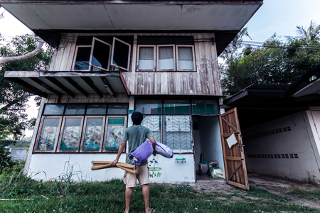 Poor man and mat with pillow stand on old wooden house with Thai style in black  tone Banco de Imagens
