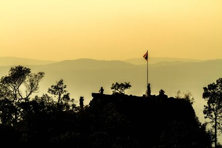 Silhouette of sunset and light flare at the mountain named Pha Chu Thong at Phu Hin Rong Kla National Park, Phitsanulok Province, Thailand