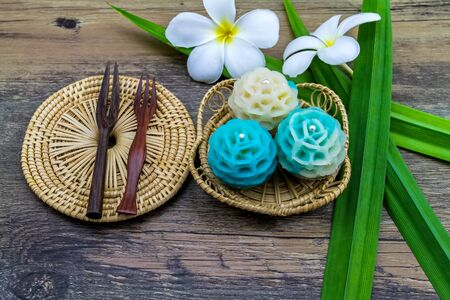 Traditional Thai dessert flower shape stuff with crush soybean and taro (Thai name kanom Chor phaka) in bamboo basket on wooden background.