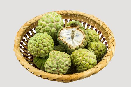 Close up ripe Custard apple  in bamboo basket  on white background.Saved   .