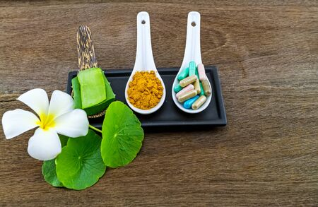 Spa herbal ( white frangipani flowers ,turmeric powder in white spoon ,pill,Aloe vera essential oil and gel,Green Asiatic Pennywort ) on wooden background Stock Photo