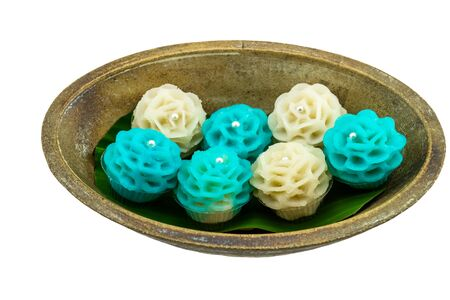 Traditional Thai dessert flower shape stuff with crush soybean and taro (Thai name kanom Chor phaka) in wooden basket on fabric sisal isolated on white background.