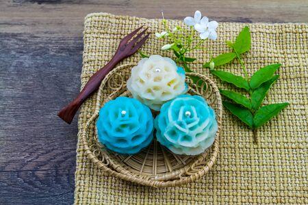 Traditional Thai dessert flower shape stuff with crush soybean and taro (Thai name kanom Chor phaka) in bamboo basket on fabric background.