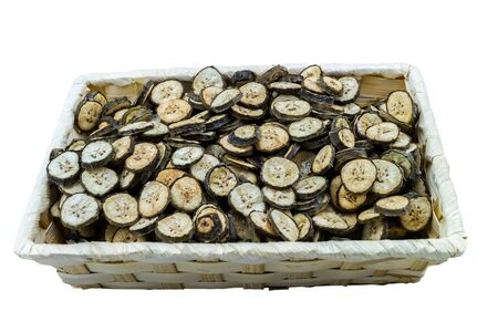 raw organic green bananas sliced spread to dry from soft sun bath in bamboo basket isolated on white background. Stock Photo