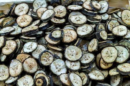 raw organic green bananas sliced spread to dry from soft sun bath on bamboo basket.