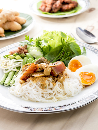 phuket food: vermicelli noodle with yellow curry, fish innards curry Stock Photo