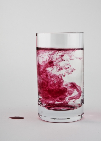 dissolved: Red paint is dissolved in a glass of clear water