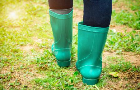 Women wear rubber boots walking in the garden.