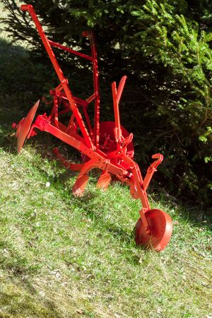 restored: old plow red restored used as decoration in the garden Stock Photo