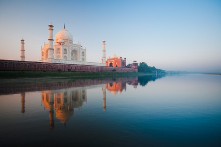 A beautiful sunrise lights the side of the Taj Mahal as seen from the Jamuna River. Banque d'images