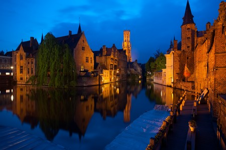 A canal reflects the buildings and belfry of the historic old city of Bruges Stock Photo