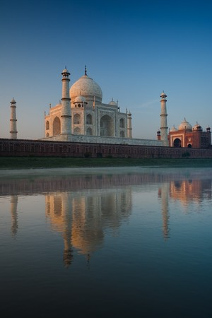 empty tomb: Daybreak reveals a majestic Taj Mahal and neighboring red mosque beautifully reflected in the gentle Jamuna river.