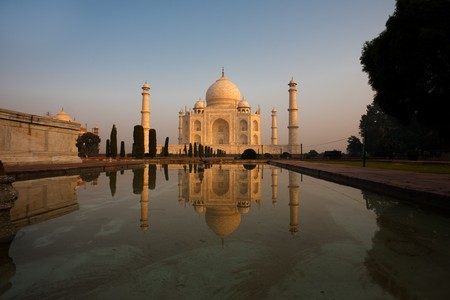 uniquely: The iconic Taj Mahal is uniquely reflected in the side central fountain at sunrise.