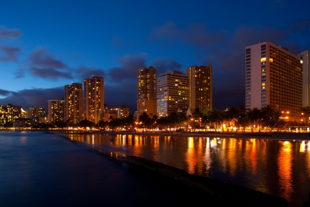 Waikikis beautiful palm lined tourist beach is brightly lighted at night. Stock Photo