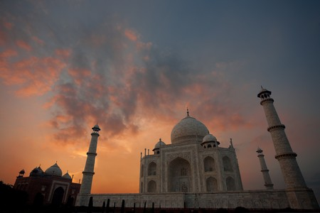 monument in india: A beautiful fiery sky highlights the clouds behind a dark and empty Taj Mahal