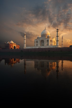 The iconic Taj Mahal and sunset sky beautifully reflected in the calmly flowing Jamuna river. Stock Photo