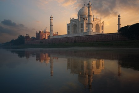 The Taj Mahal glows brilliantly from a colorful sunset seen from the holy Jamuna river.