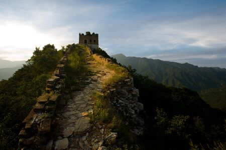 The sun sets fiery red behind a watchtower at the Jiankou section of the Great Wall of China. photo